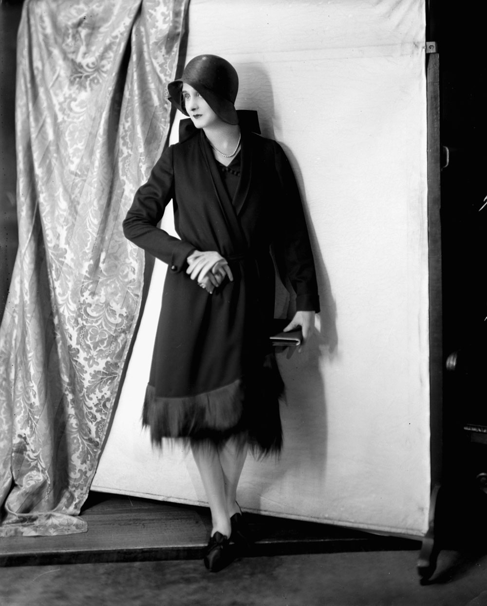 A model wears a knee-length dress and overcoat with a women's bowler hat.