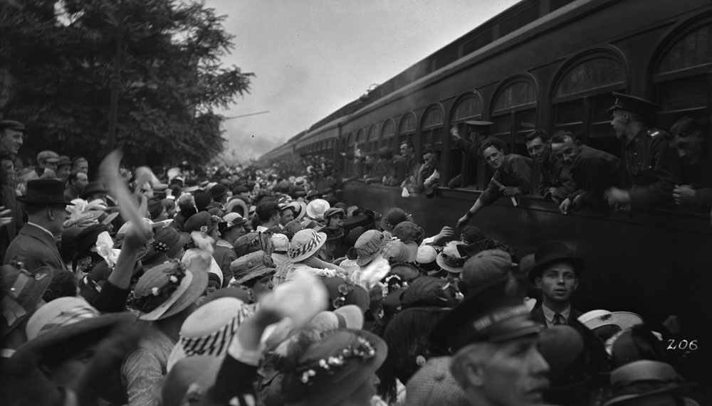 A crowd waves goodbye to soldiers departing on a train.