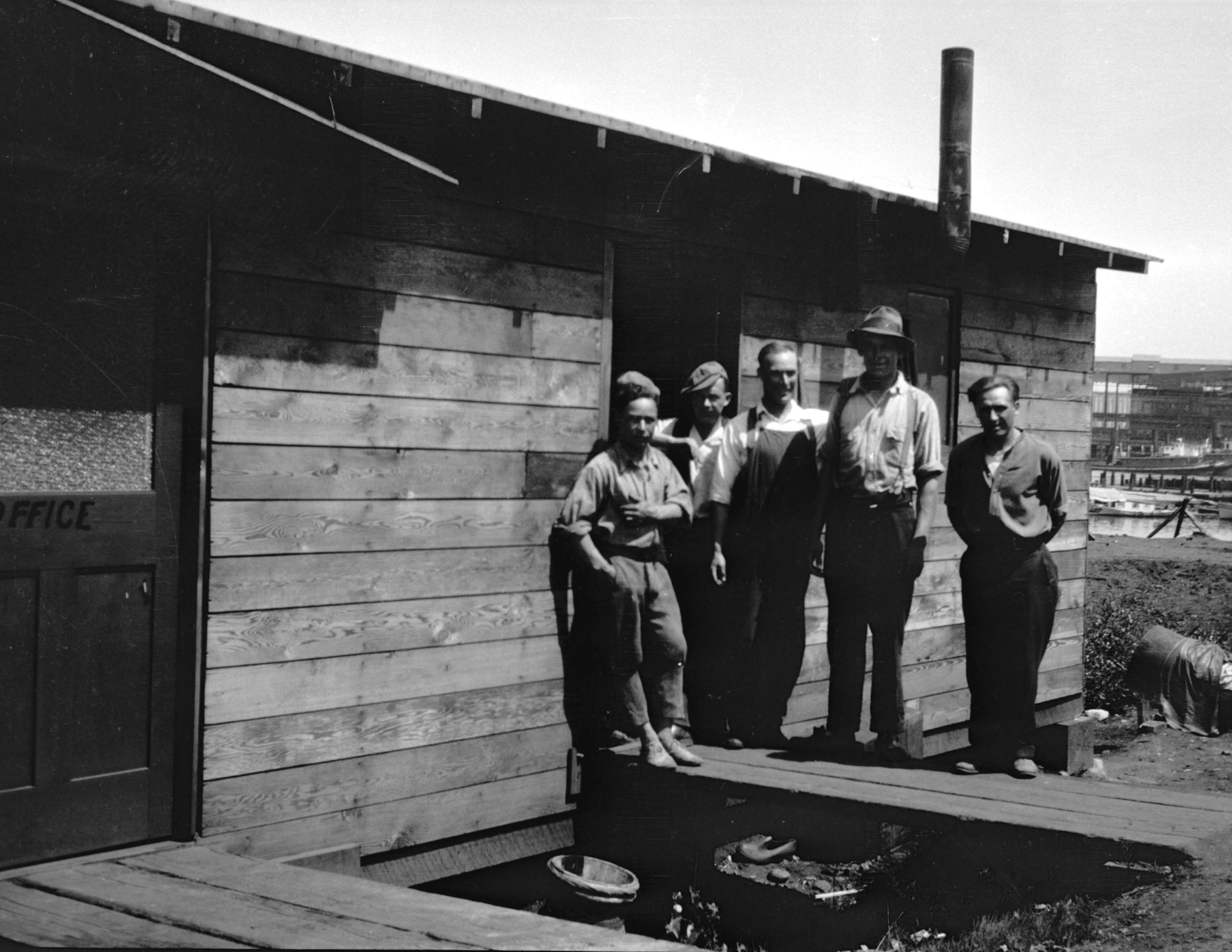 Five men stand outside of a wooden shack.