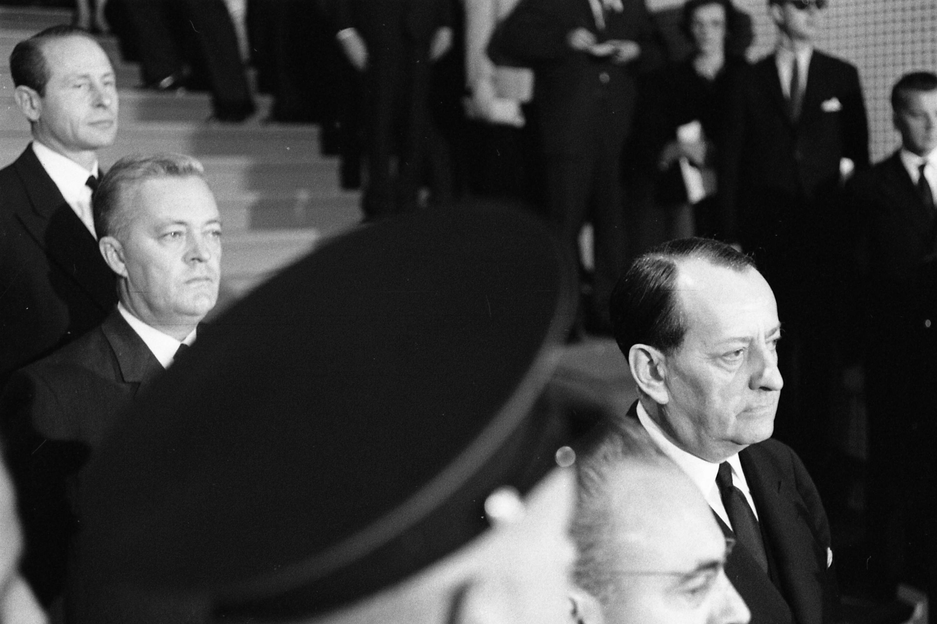 Three men in suits descend a staircase. A military officer's hat obscures most of the shot.
