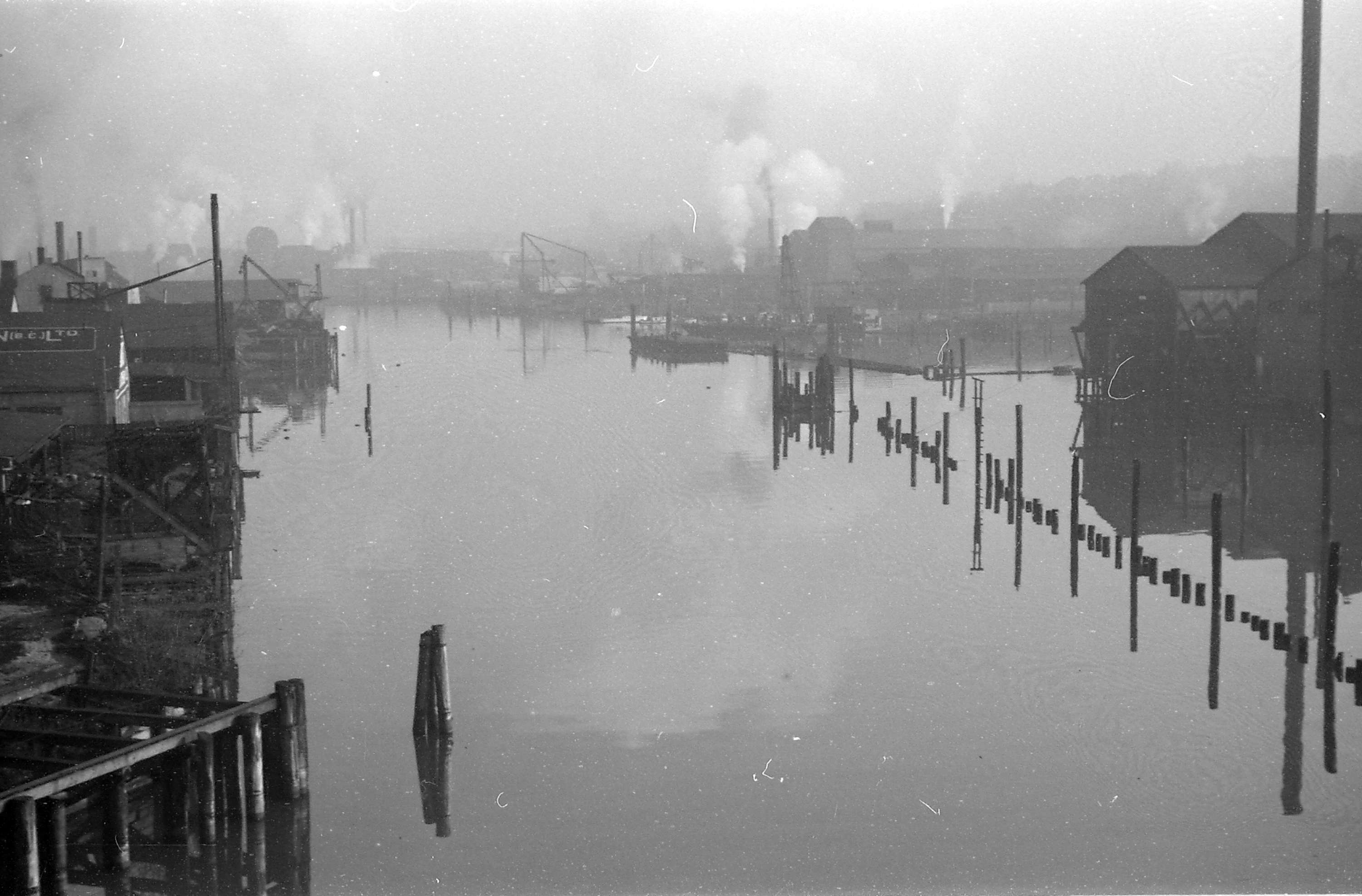 Buildings crowd the banks of a river. In the distance, smoke billows.