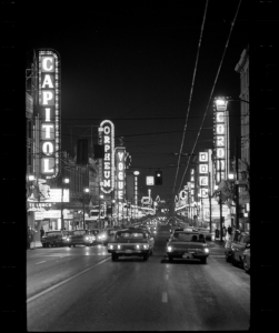 Even in the late 1960s, neon lights and rain-soaked streets in downtown Vancouver suggested film noir rather than suburban domesticity. Vancouver Public Library 43347.
