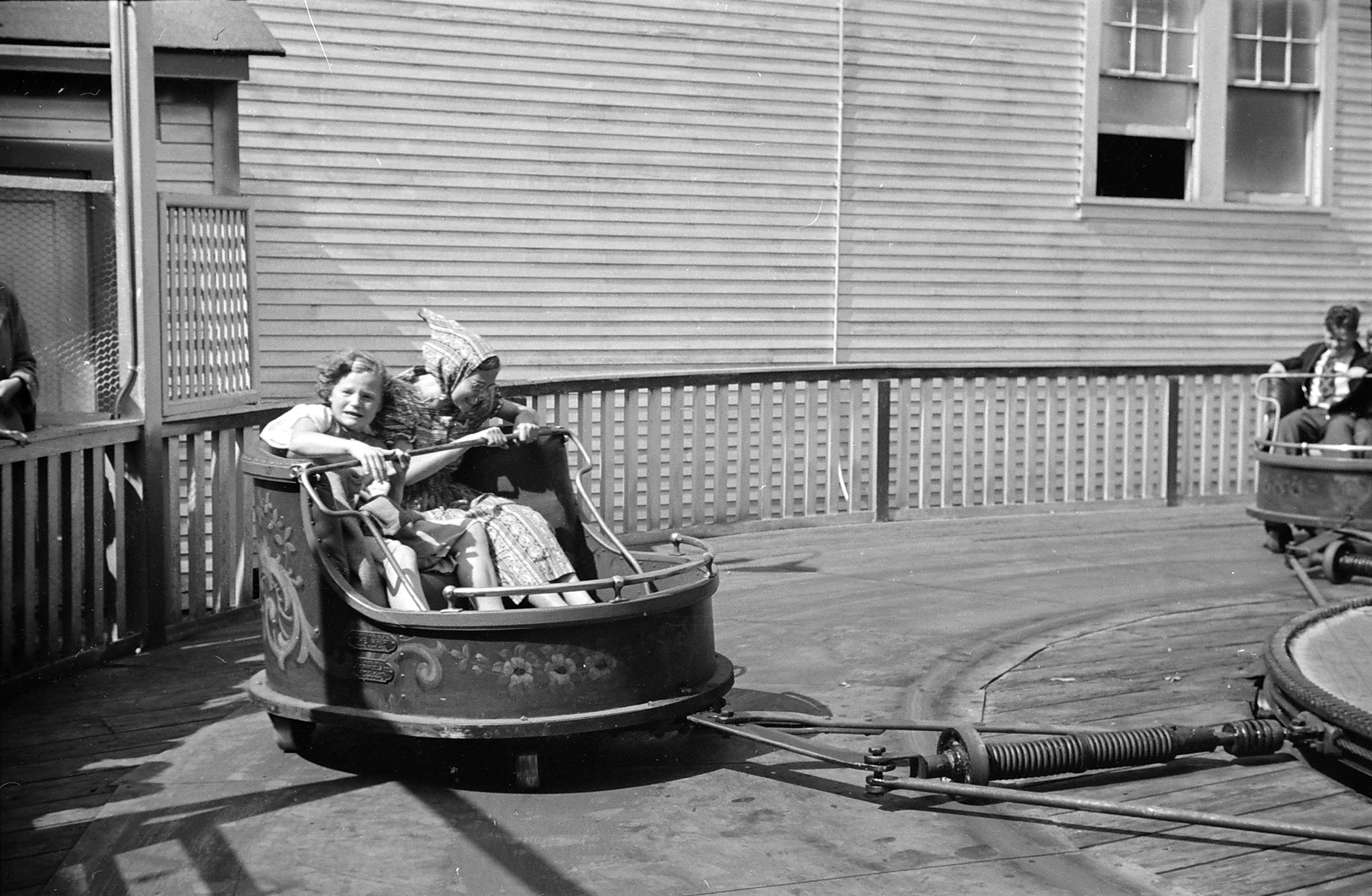 Two girls sit in a fair ride car swinging in a circle. One looks thrilled, while the other scared.