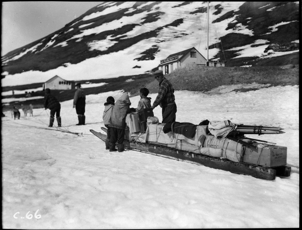 A man and three children stand around a long sled loaded with supplies.