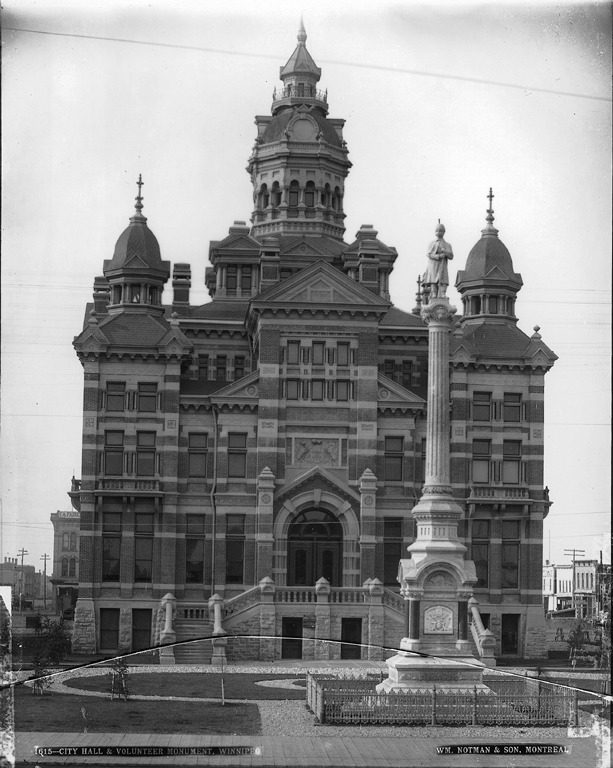 Tall, ornate city hall. In front is a tall, skinny monument with a statue of a man on top.
