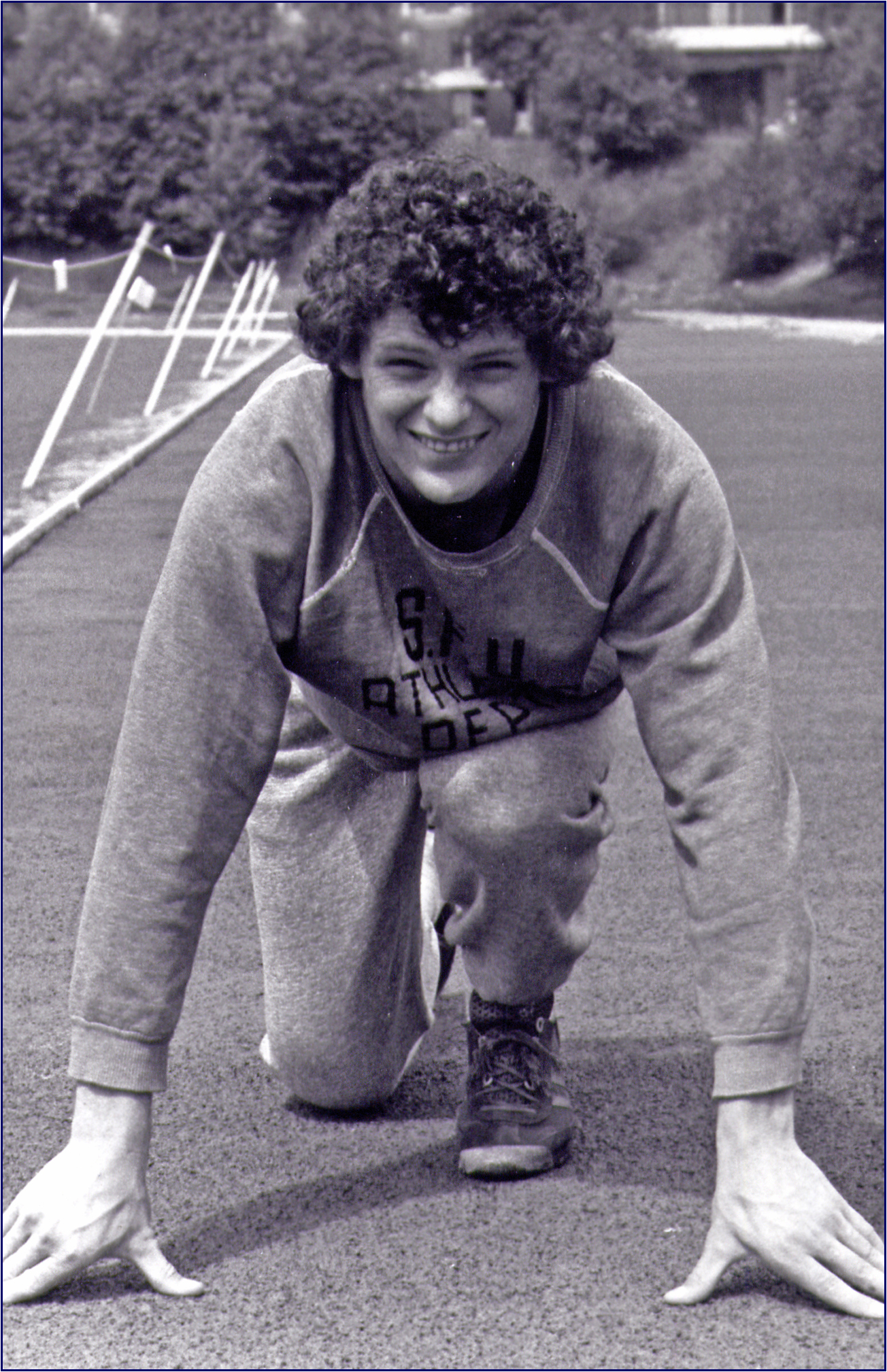 A smiling young man with curly hair wearing a tracksuit poised for a crouch start.