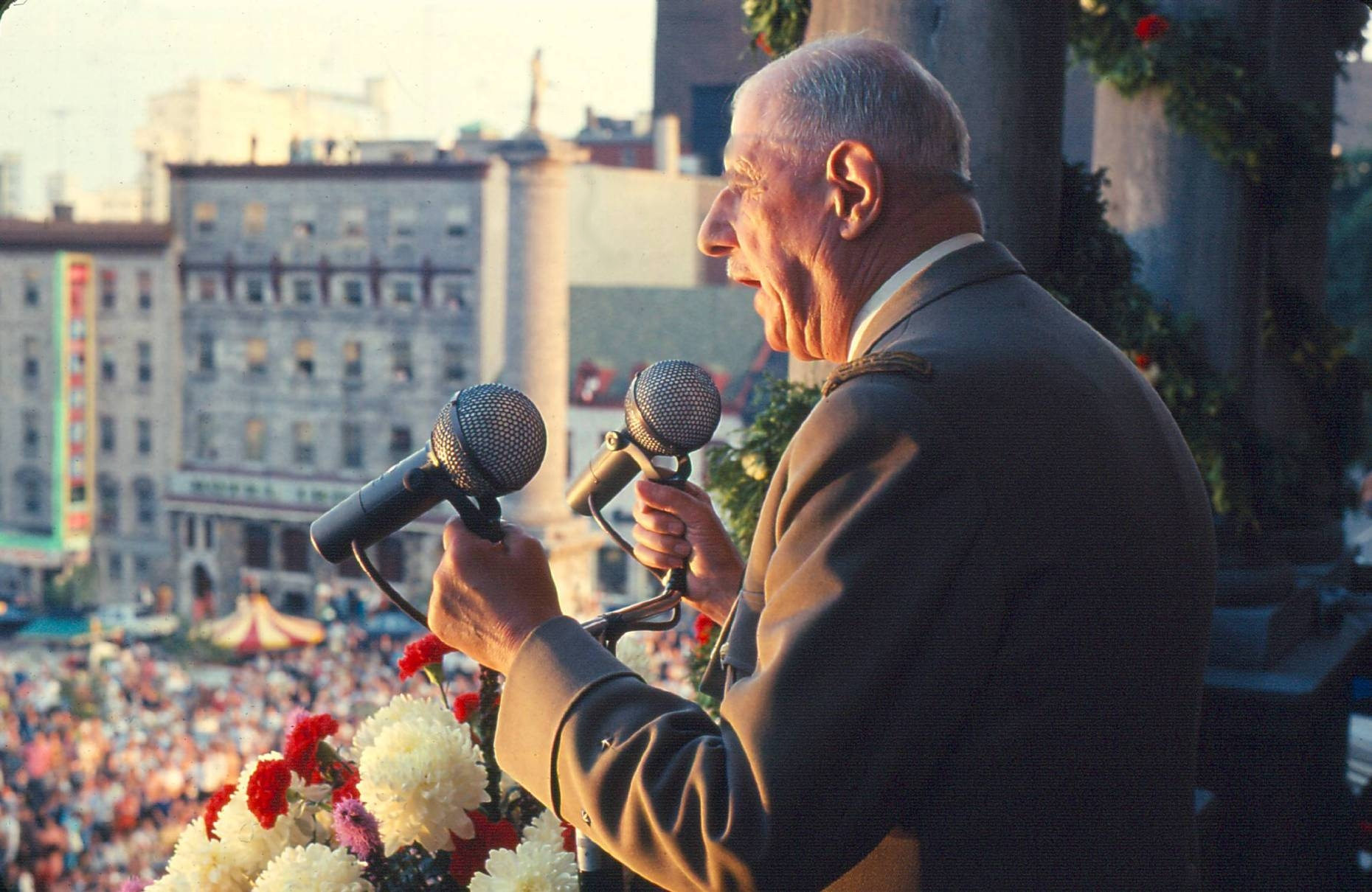 An older man on a balcony grips two microphones and addresses an unseen crowd on the street.