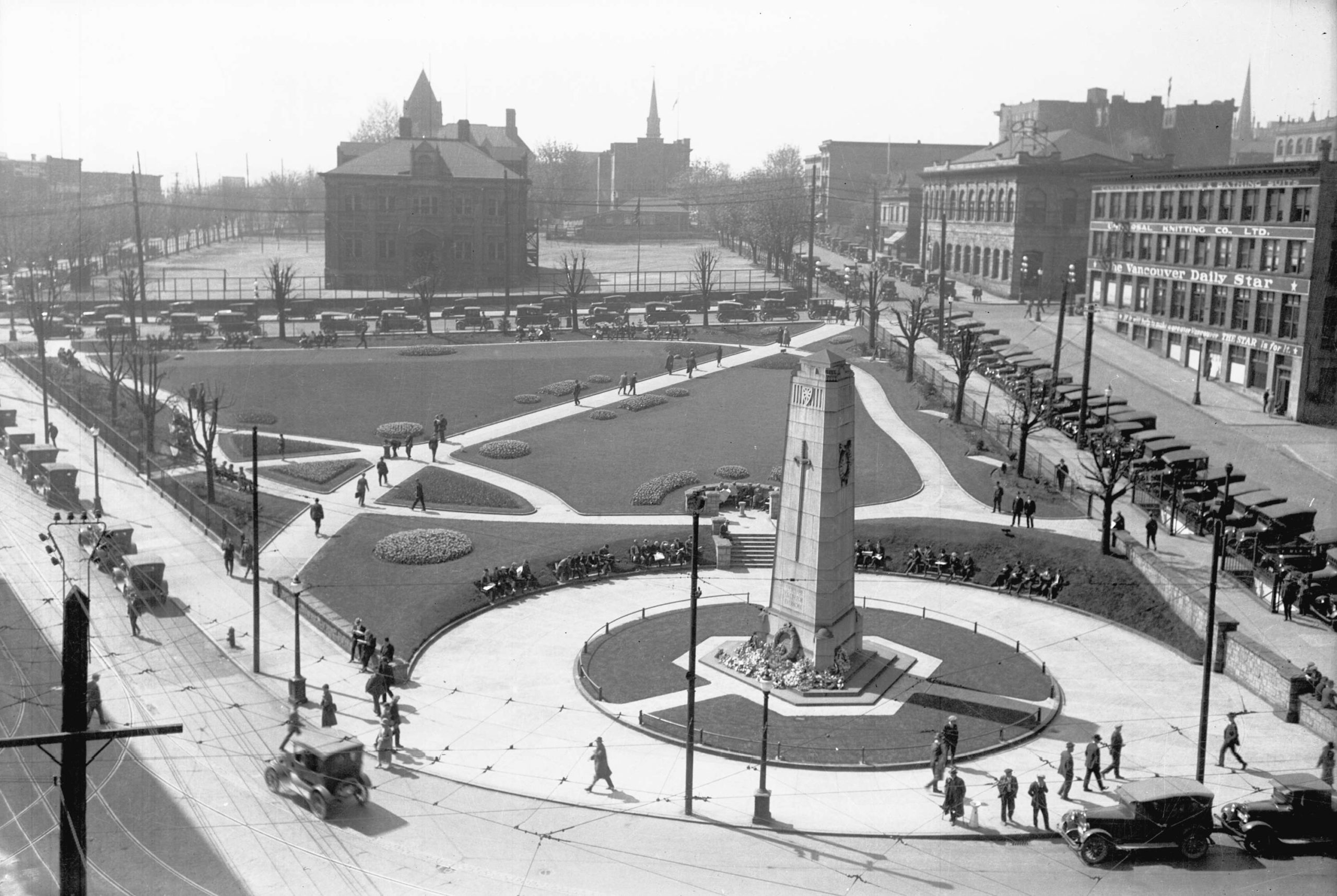 Rectangular stone memorial is the focus of a city square. Landscaping and buildings surround it.