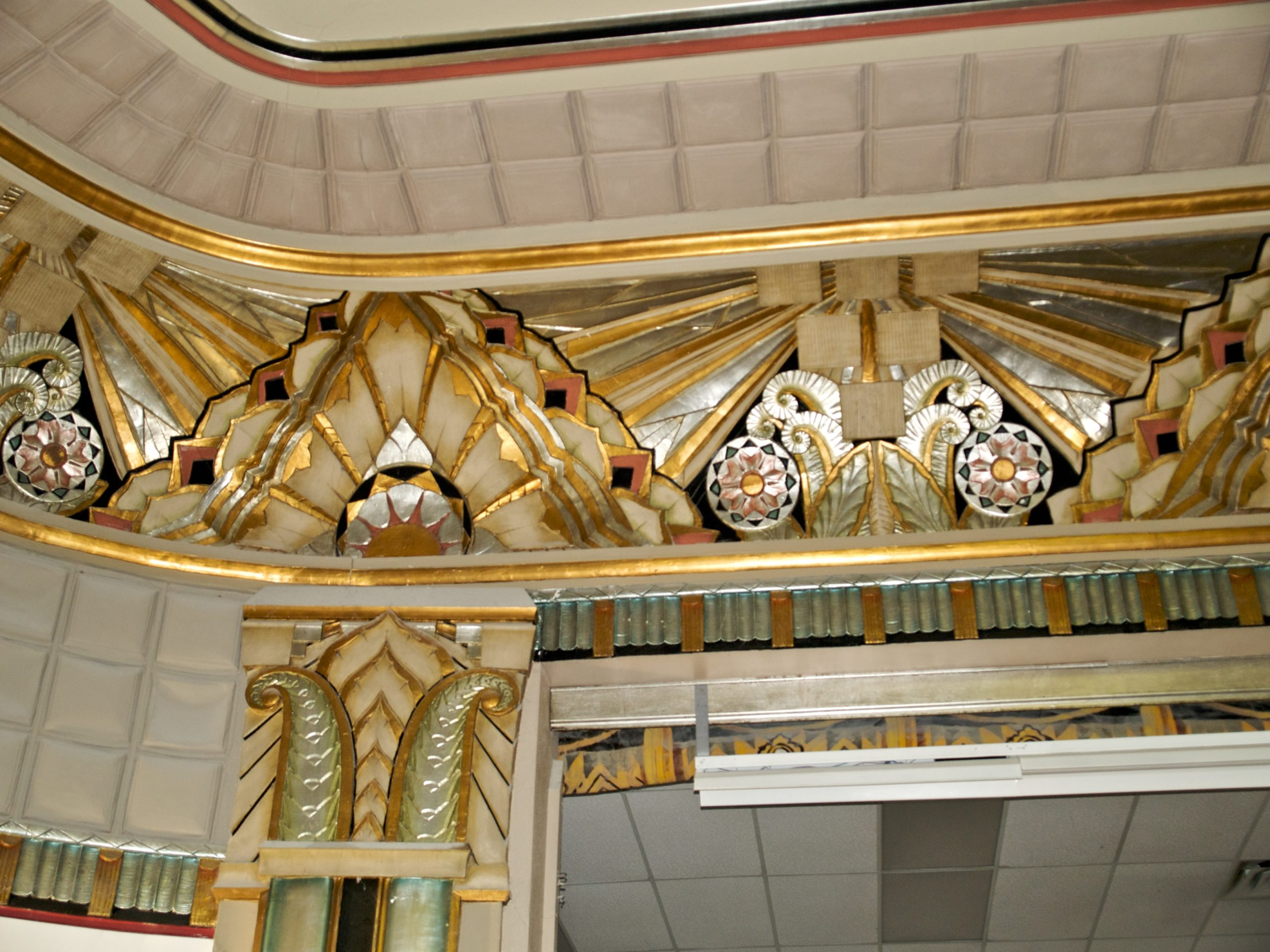 Ornate gold and silver leaf decorations in the ceiling of a building.