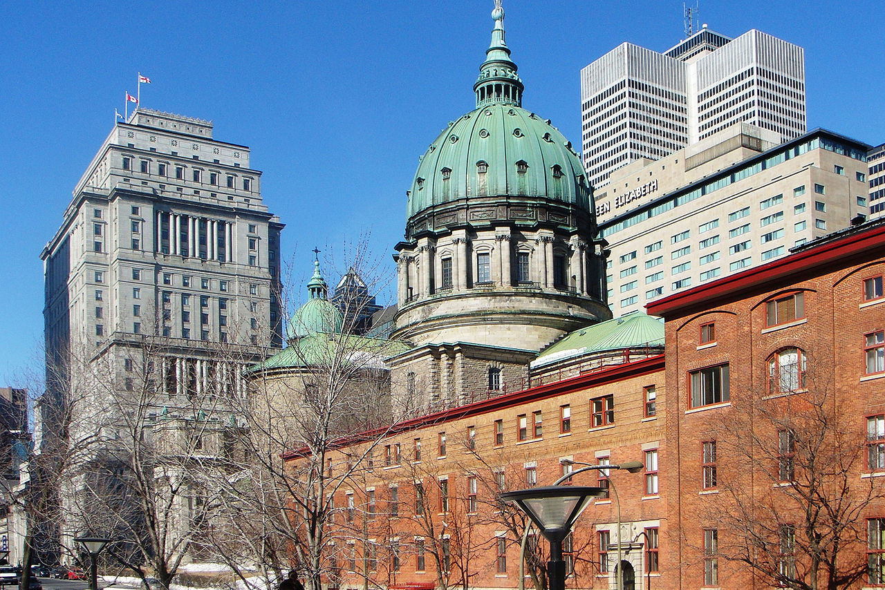 A building with a stone facade and copper domes turned green. It is surrounded by tall office buildings.
