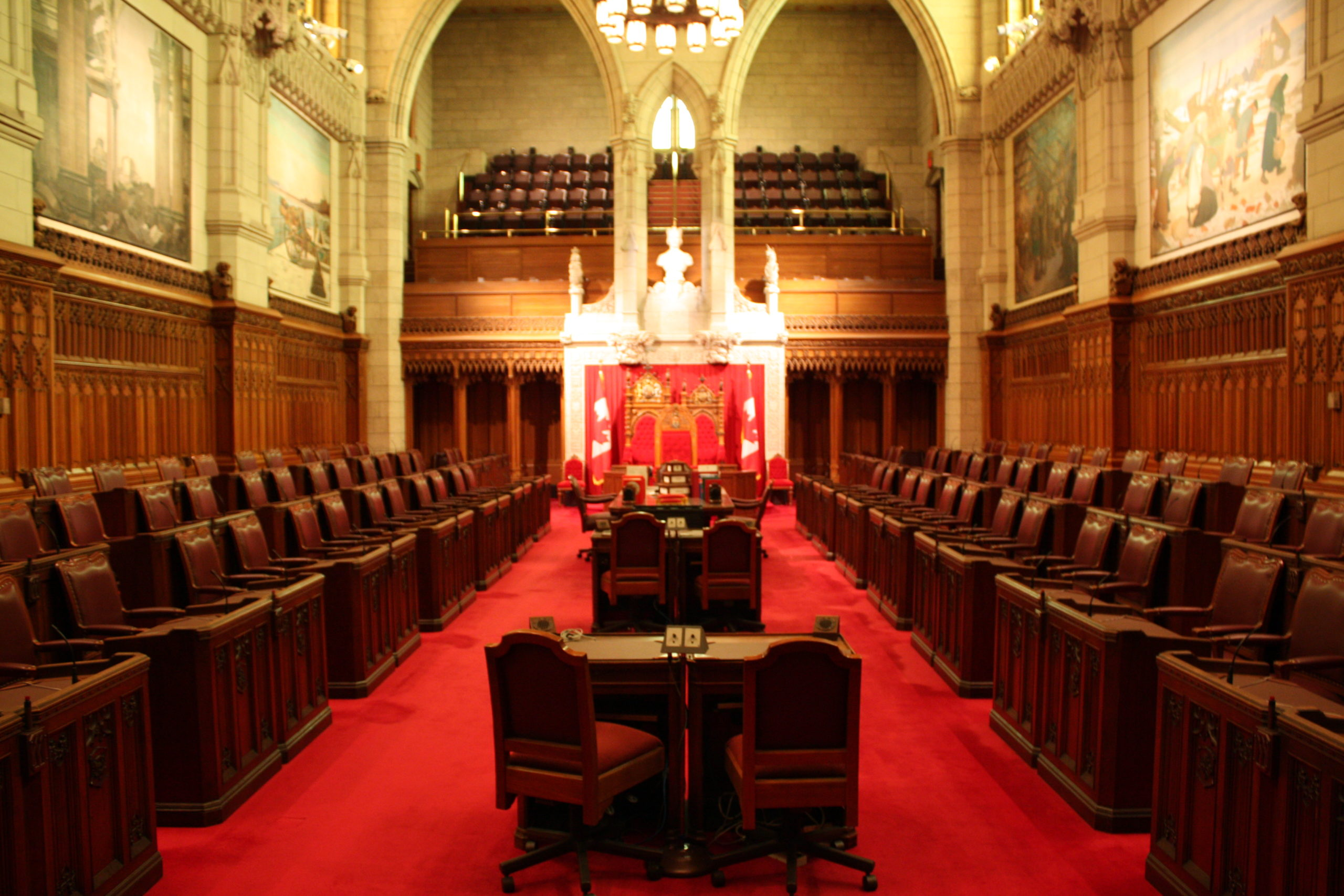 Parliamentary chamber with rows of chairs and desks, a red carpet, and a gallery.