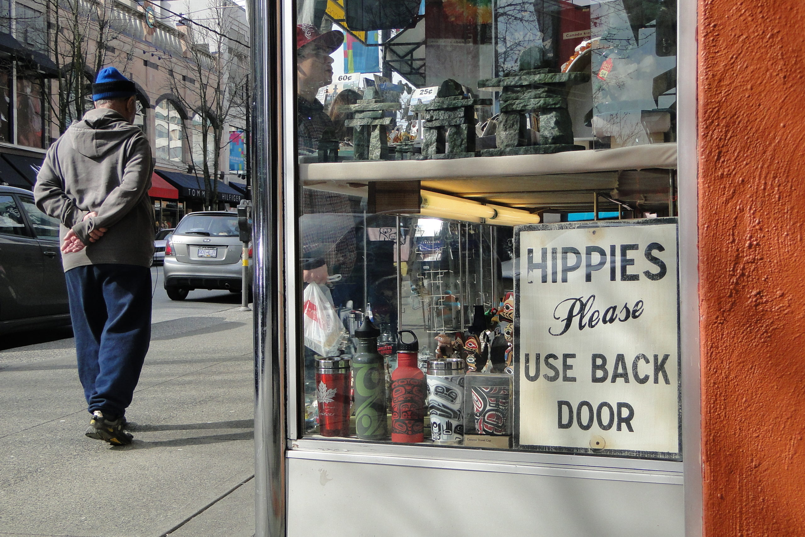 """A sign in a storefront says """"Hippies please use back door."""""""