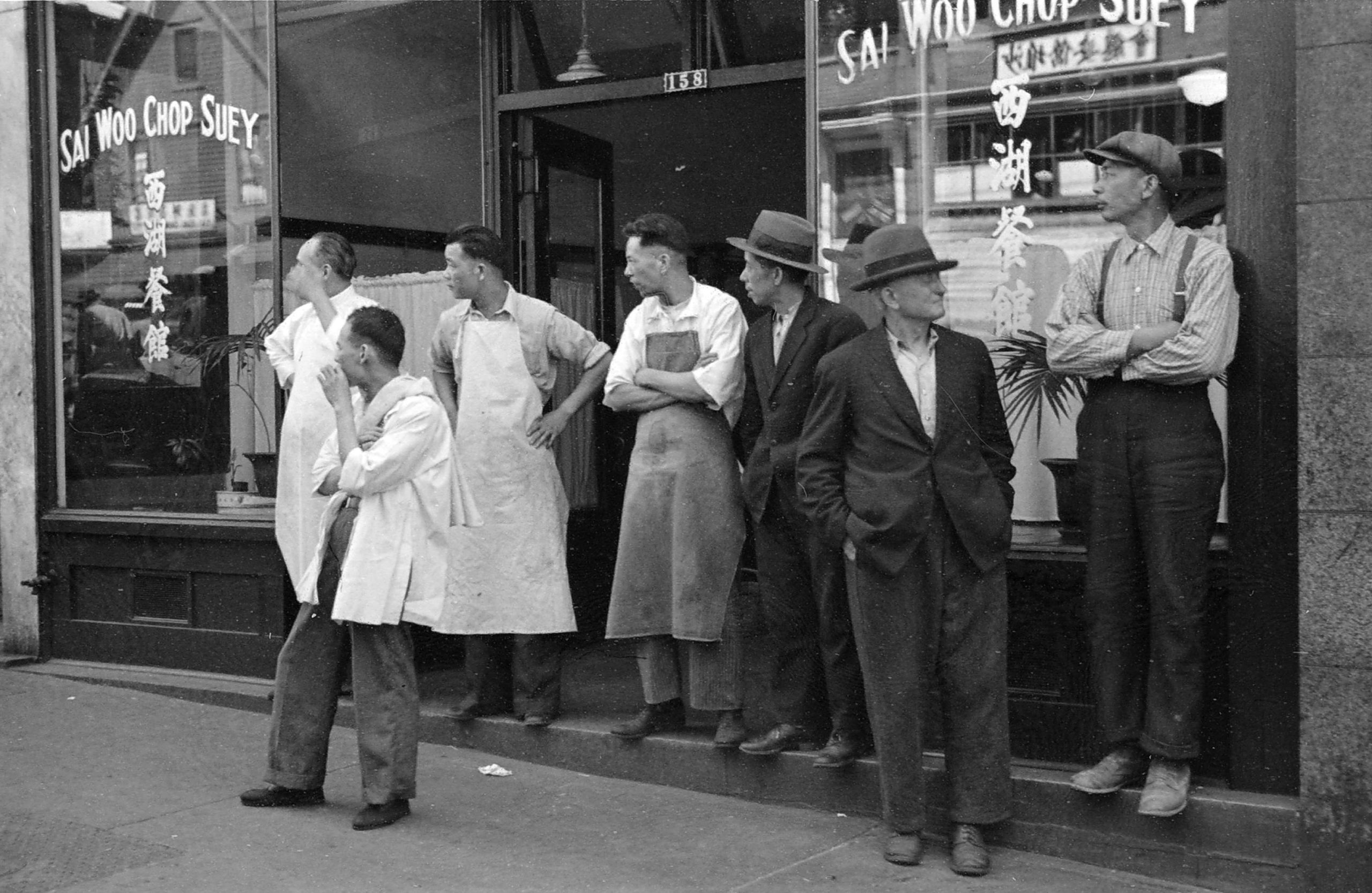Seven men stand outside a restaurant, some dressed like kitchen workers and others in suits.