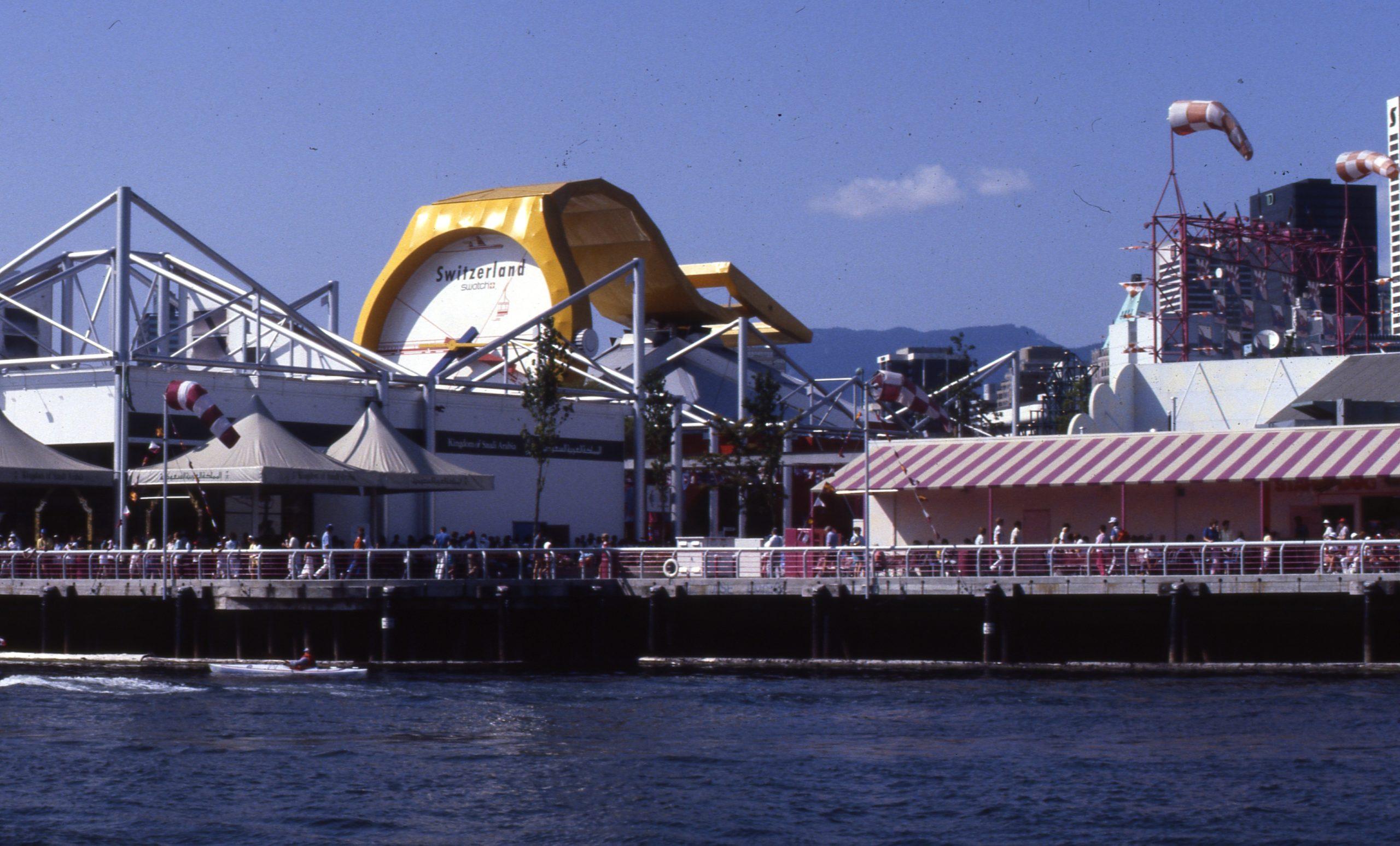 Crowds walk around a harbour. Above a building rises a golden pavillion for Switzerland.
