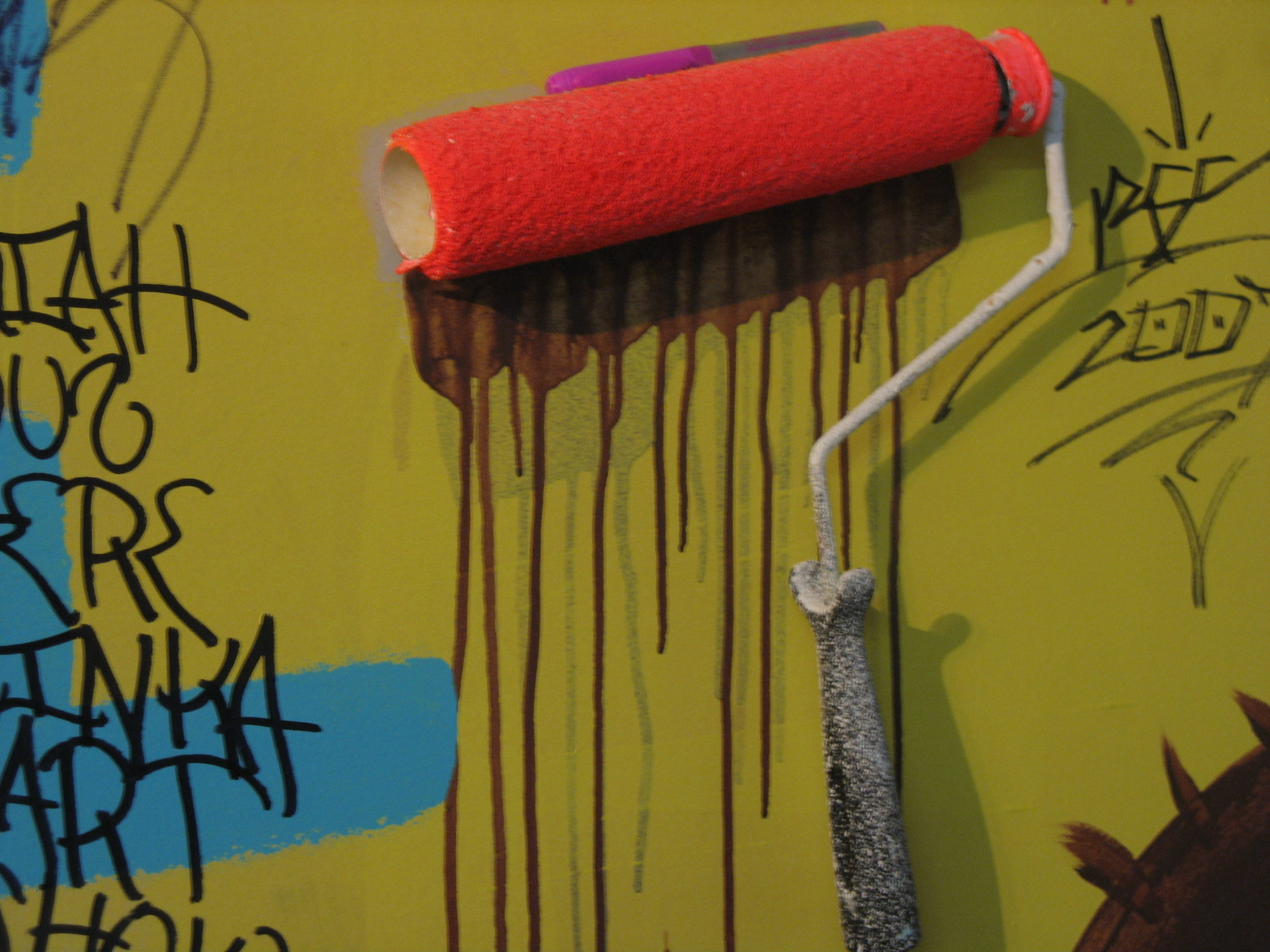 An orange paint roller is pushed against a wall. Paint drips down the wall beneath it.