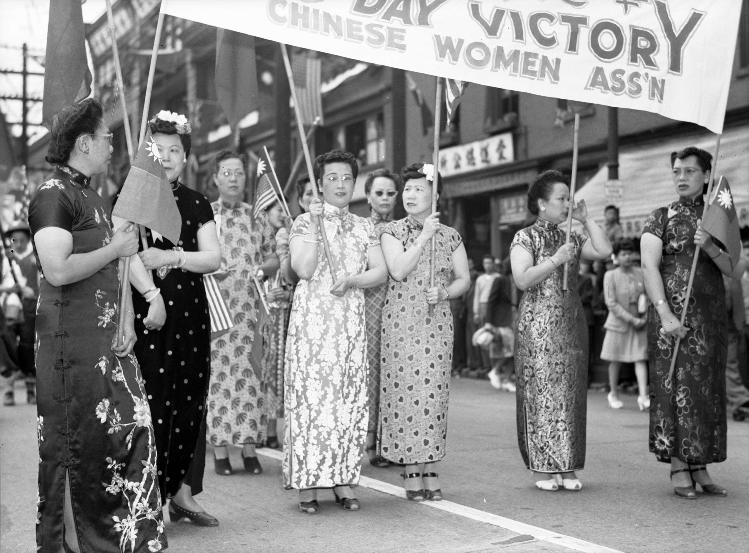 Several middle-aged women wearing qipaos walk down the street hoisting a victory banner.
