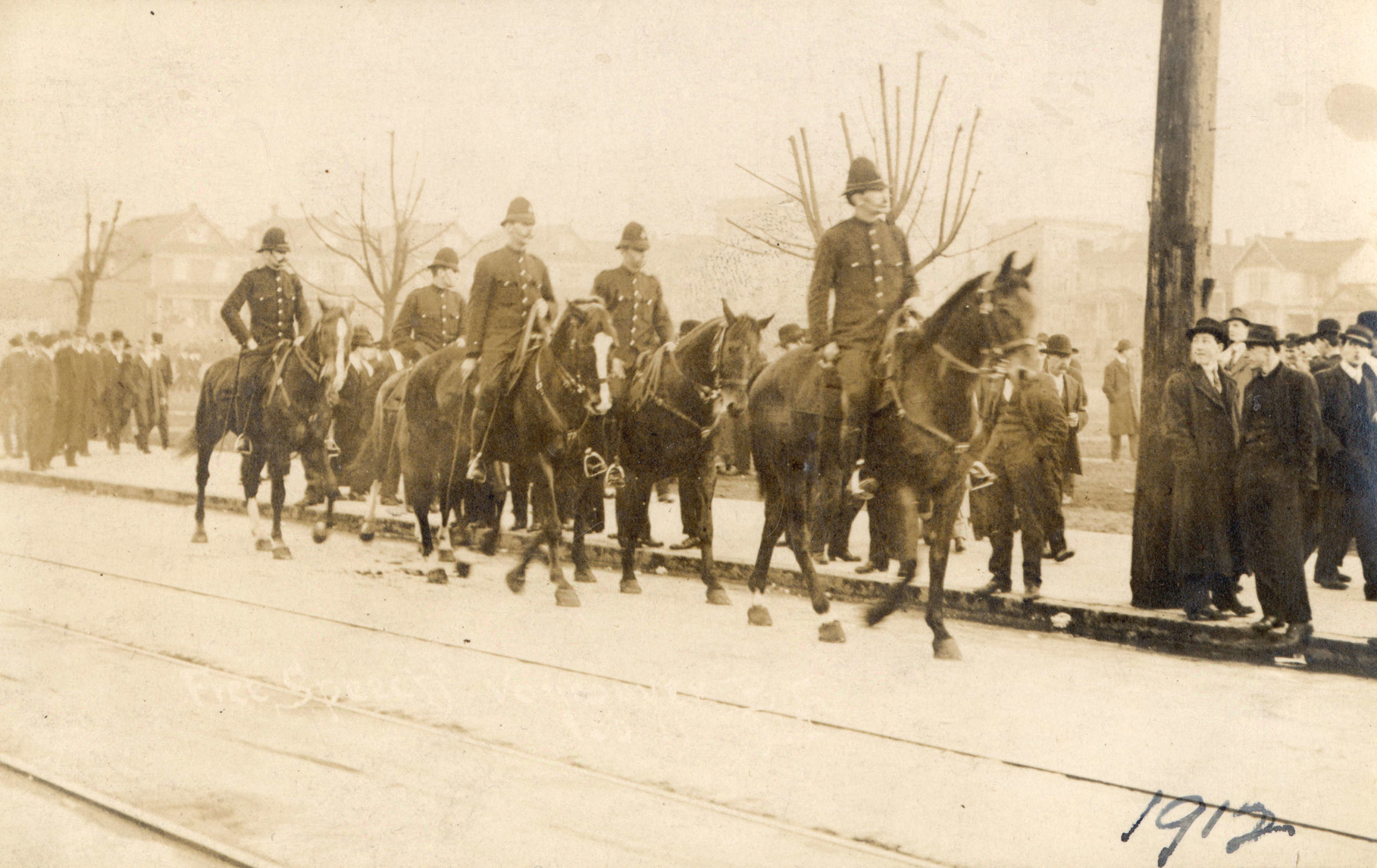 Five policemen ride horses down a city street with people gathered on the sidewalks.