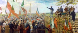 A man on a stage adresses a crowd. Pople in the crown wave flags.