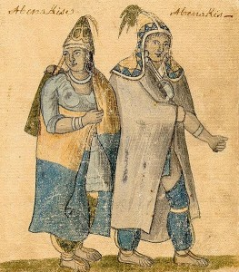 A man and a women wearing loose clothing, pointy hats, and blankets worn like capes.