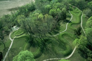An aerial shot of raised earth covered in grass in the shape of a winding snake.
