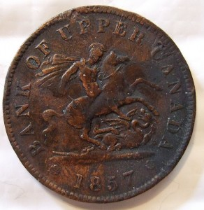 A copper coin that says, Bank of Upper Canada, 1857. A man is pictured in armor on a rearing horse