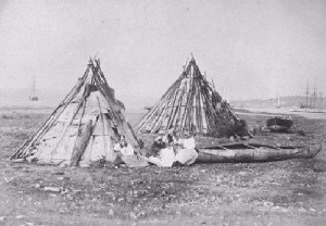 People sit outside of two teepees. A canoe sits beside them.