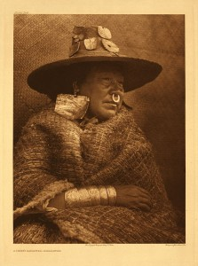 A woman with large, square earlings, a woven hat and blanket, a nose ring, and bracelets.