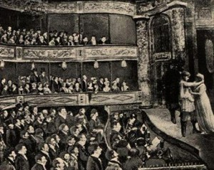 People in suits and fancy clothes sit in the audience and watch actors on the stage.