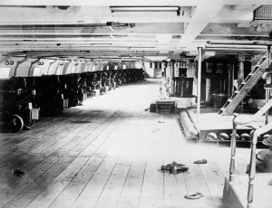 A long row of guns facing out of windows in a boat.