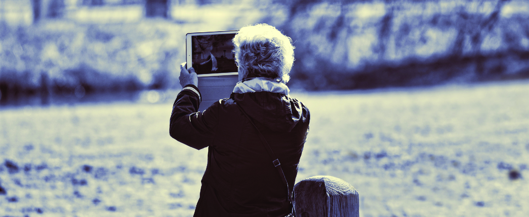 Picture of a person in a field by a stream holding up a computer tablet.