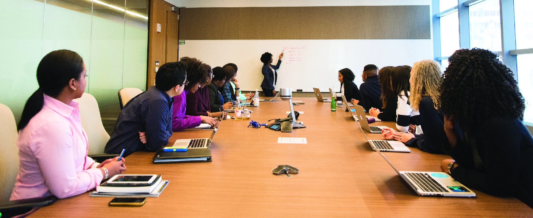 A photograph shows a group of people with laptops and notebooks sitting around a large conference table and looking up at someone writing on a board.
