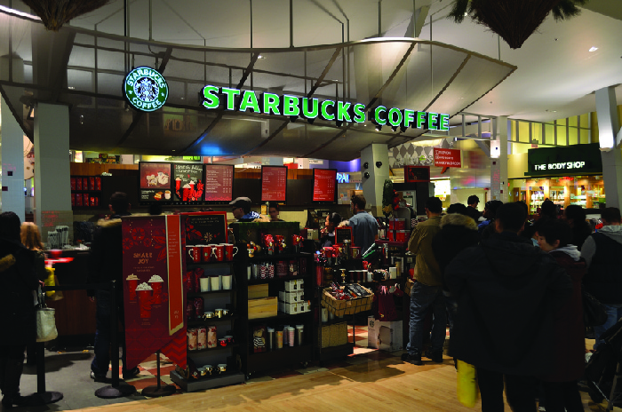 A picture of the inside of a Starbucks store showing shelves of items for sale.