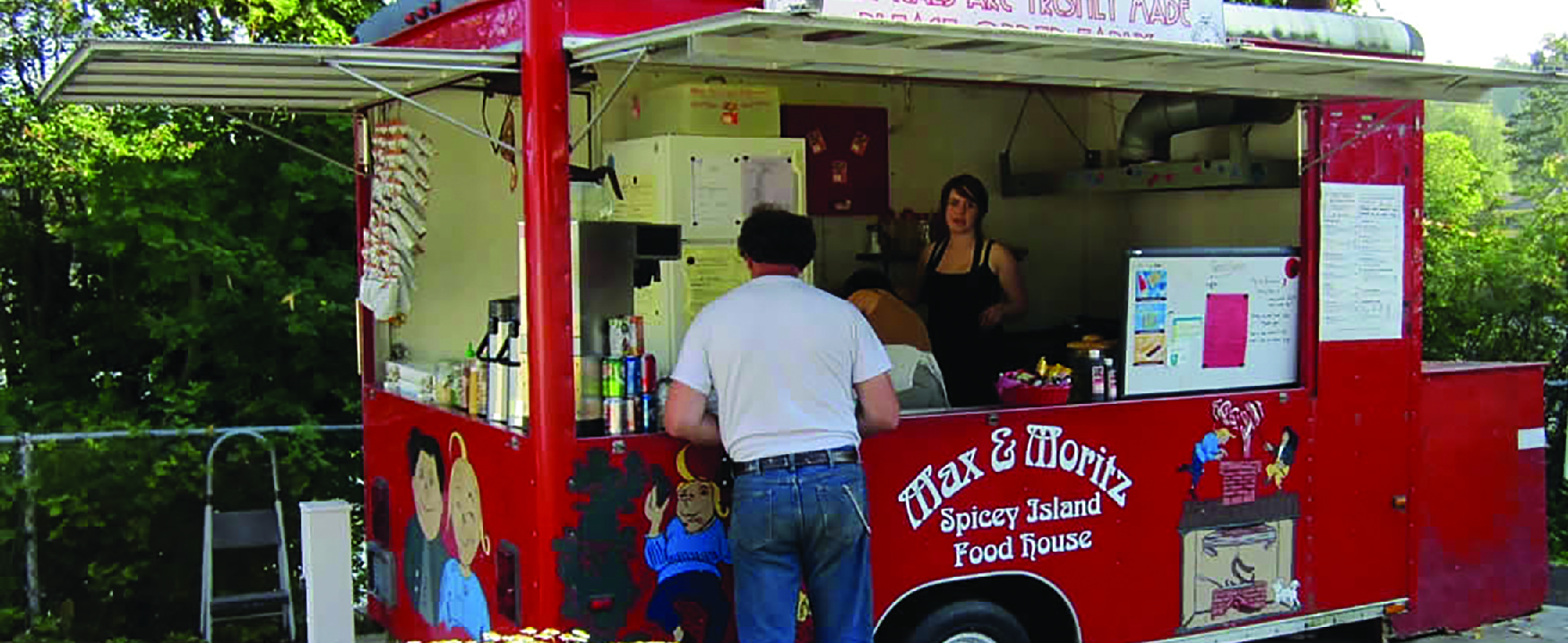 Picture of two people in a food truck serving a customer.