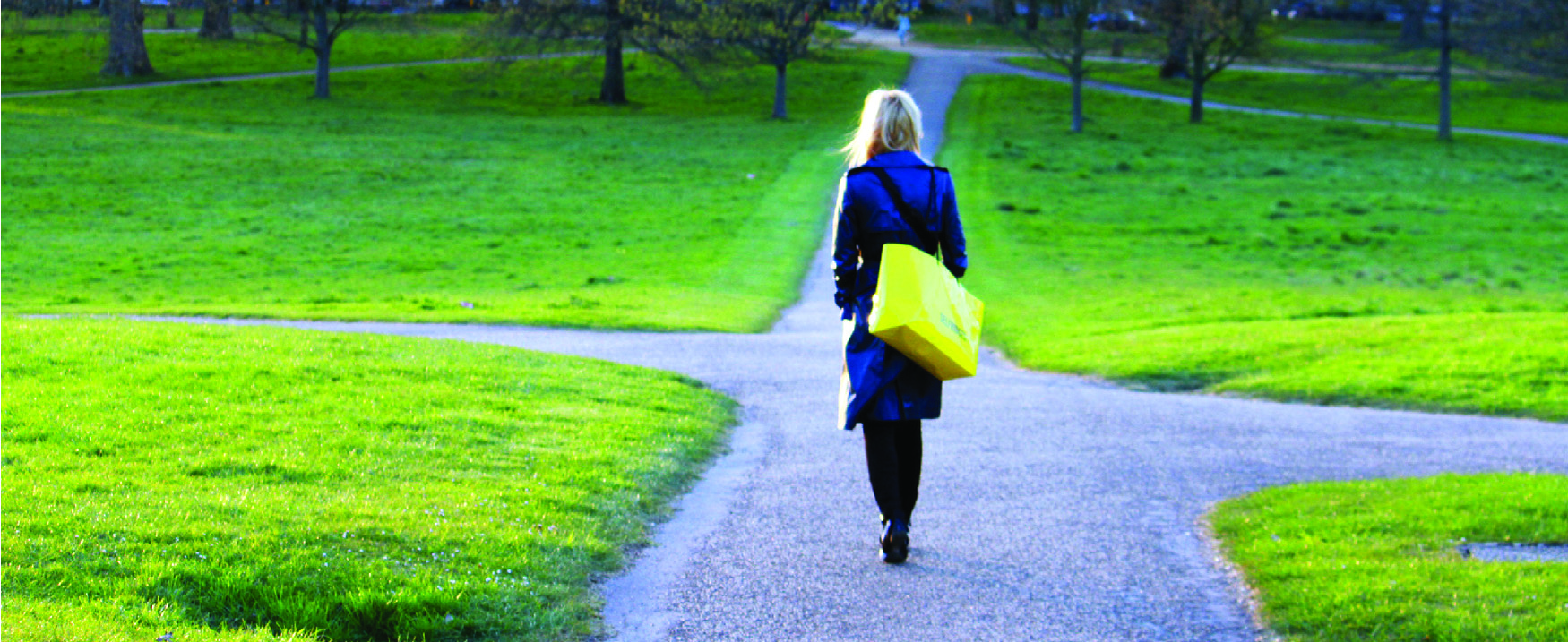 A photograph of a woman walking on a path that branches off in different directions.