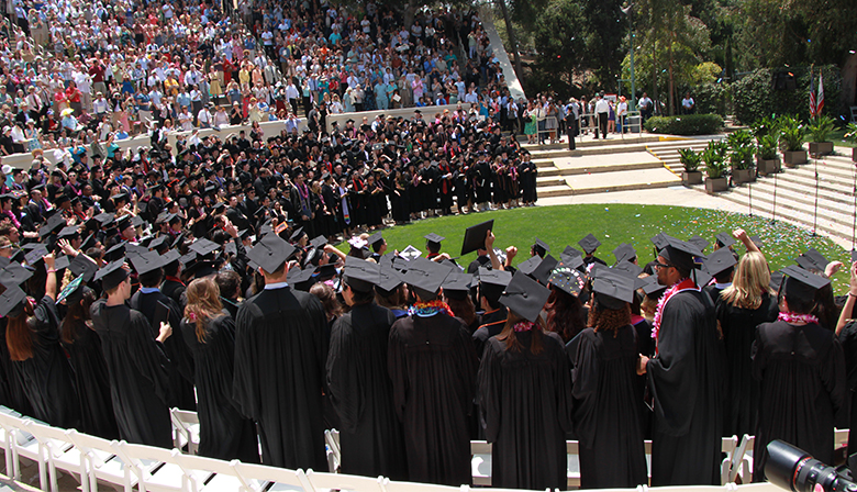 This is a photograph of students at their outdoor college graduation ceremony.