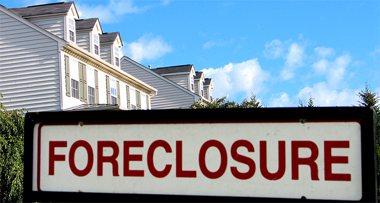"""The image shows a """"Foreclosure"""" sign in the foreground and the tops of a couple of houses in the background."""