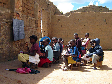 "This is an image of children sitting in a ruined structure which serves as their outdoor ""classroom."""
