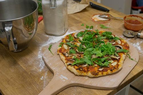 Image of a pizza peel with mushroom and arugula.