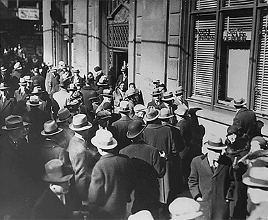 This image is a photograph of people lining up outside of a bank in hopes of withdrawing their funds during the Great Depression.