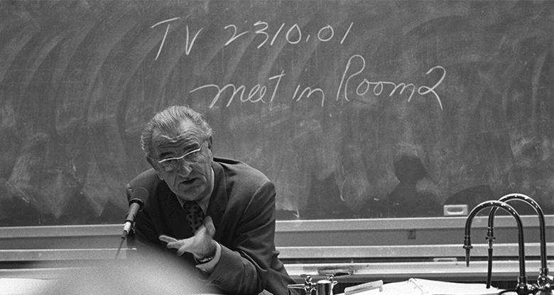 This is a photograph of Lyndon B. Johnson in front of a chalkboard.