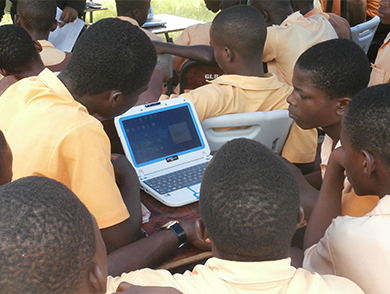 This photograph shows several students gathered around a single laptop that has been powered with solar energy.