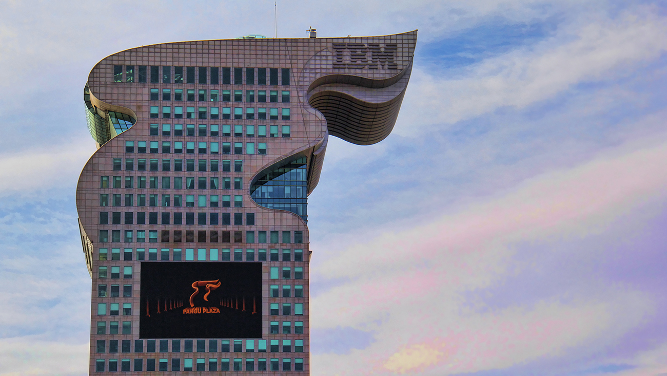 A photo shows a close-up of the Dragon Building, I B M's headquarters based in China, against a clear blue sky.