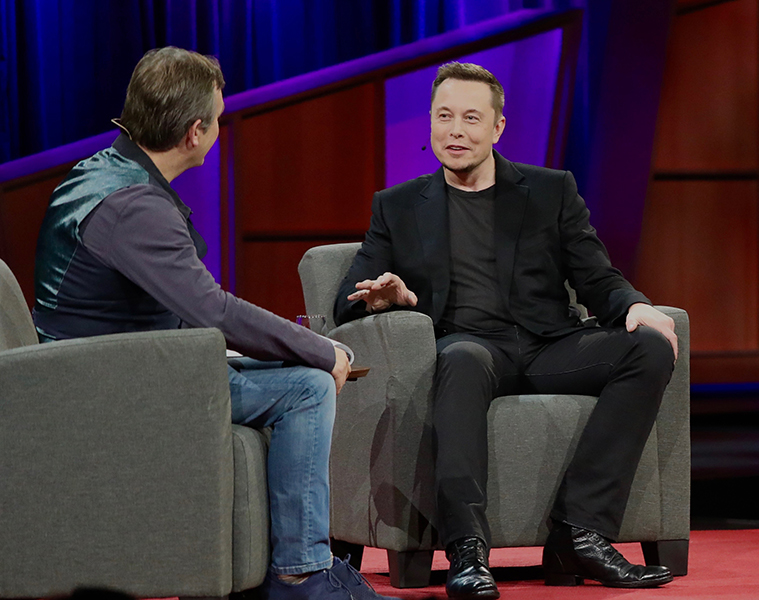 A photo shows Elon Musk in conversation with the host at a Ted X conference.