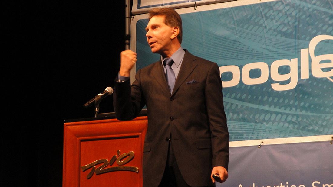 A photo shows the American psychologist Robert Cialdini clenching his fist as he delivers a speech.