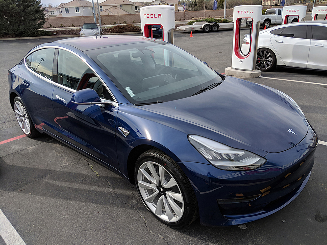 A photo shows a Tesla Model 3 electric car pictured at one of its supercharger stations.
