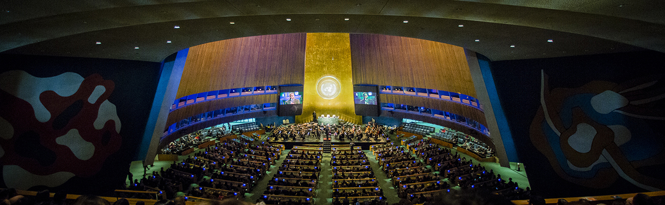 A photo shows a view of the General Assembly Hall, with Alan Gilbert leading the New York Philharmonic on stage to pay a tribute to Ban Ki-moon at the completion of his 10-year term.