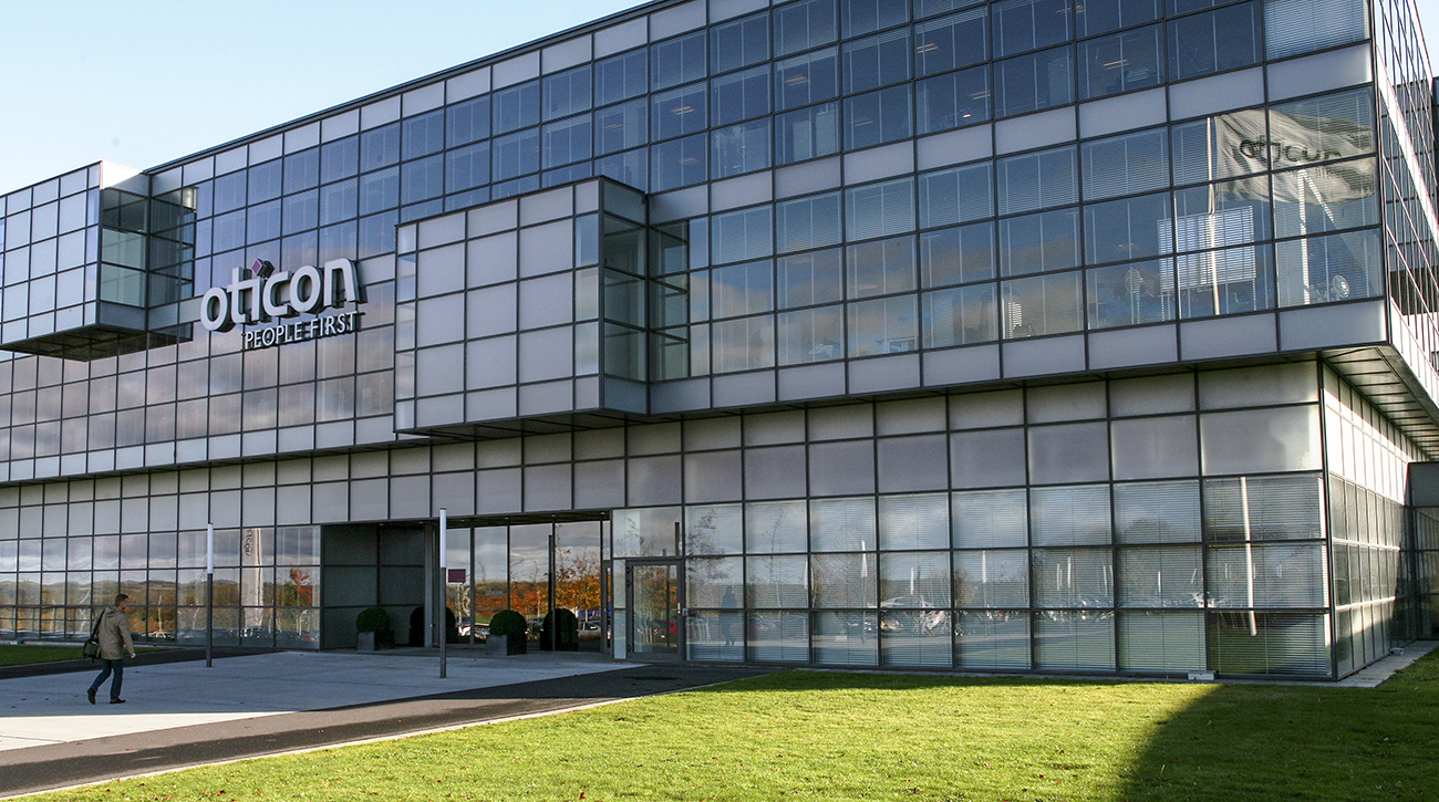 A photo shows the front view of the headquarters of Oticon, featuring modern architectural features.