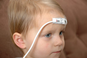 Pulse oximeter with sensor taped across forehead.