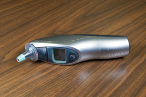 A tympanic thermometer with probe cover on.