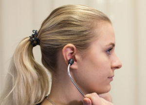 The healthcare provider is demonstrating a correct technique of inserting stethoscope in ears with ear pieces directed forward or toward nose